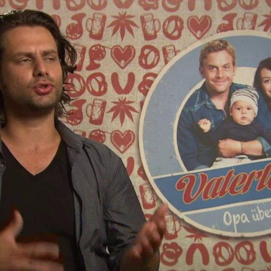 Adam Bousdoukos -Nektarios- über Unterschiede der griechischen zur deutschen Familie - Interview Poster
