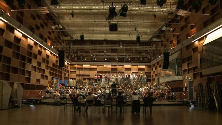 Panoramaaufnahme des Saals mit Orchester - Making Of Poster