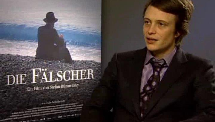 Interview mit August Diehl (Adolf Burger) über die besondere Lage der KZ-Häftlinge im Fälschertrakt in Sachsenhausen und über ihren Kampf ums Überlebe Poster