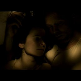 Eugenia und Anton liegen zusammen im Bett und reden über seine verstorbene Frau und Kinde - Szene Poster