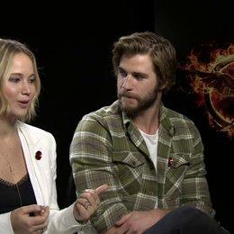 Jennifer Lawrence - Katniss Everdeen - und Liam Hemsworth - Gayle Hawthorne - über das Verhältnis der drei Hauptdarsteller - OV-Interview Poster